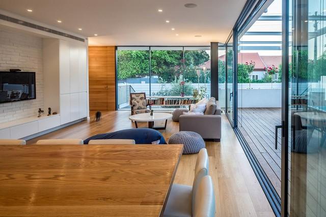 Aménagement d'un petit salon moderne ouvert avec une salle de réception, un mur blanc, un sol en bois clair et un téléviseur fixé au mur.
