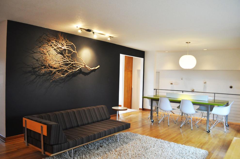 Example of a mid-century modern loft-style medium tone wood floor living room design in Portland with black walls