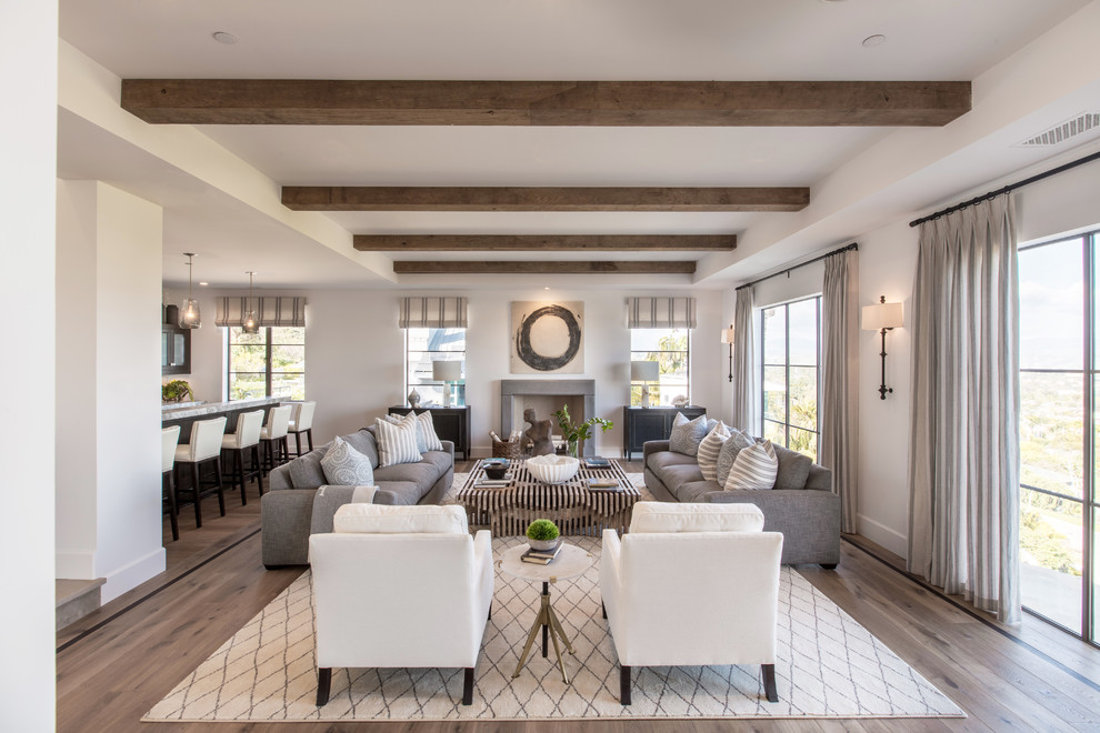 Inspiration for a transitional open concept dark wood floor and brown floor living room remodel in Orange County with white walls and a standard fireplace