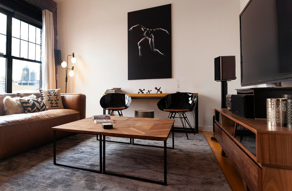 Inspiration for a mid-sized industrial medium tone wood floor and brown floor living room remodel in Philadelphia with white walls and a wall-mounted tv