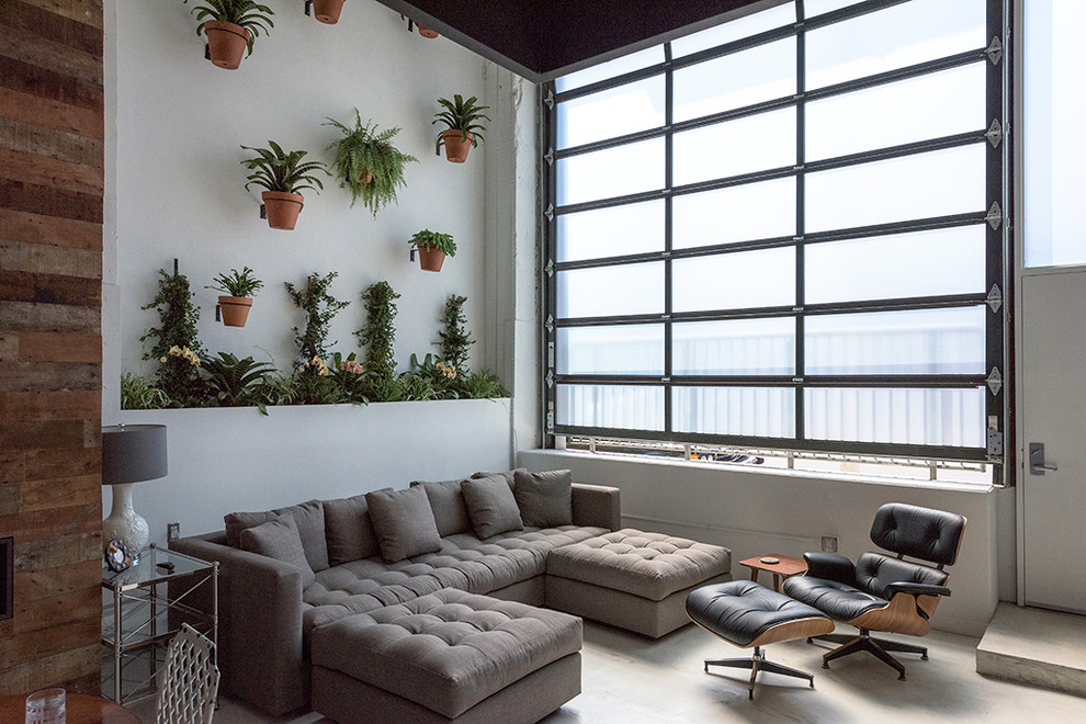 Inspiration for an industrial formal and open concept concrete floor living room remodel in Los Angeles with white walls
