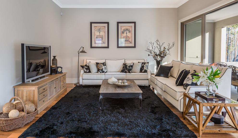Living room - mid-sized traditional open concept medium tone wood floor and brown floor living room idea in Melbourne with beige walls and a tv stand