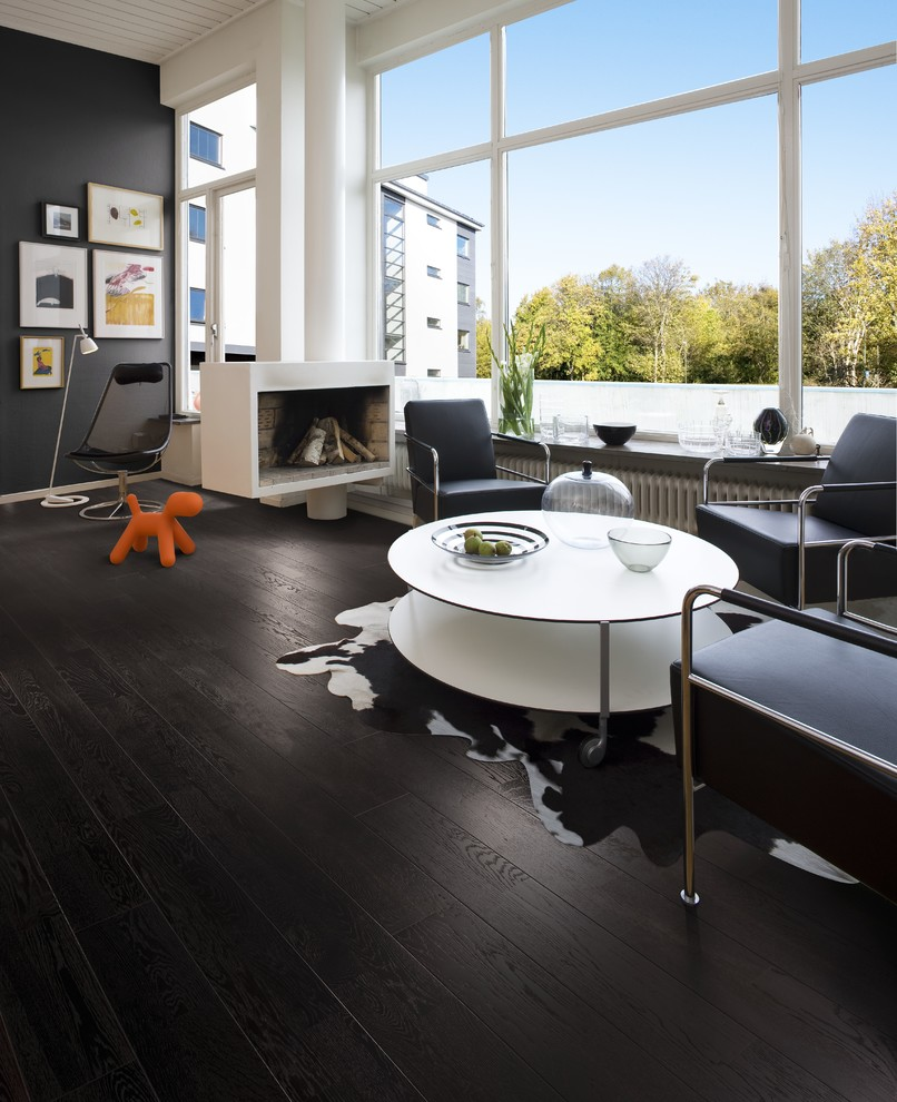 Living room - large 1950s open concept dark wood floor living room idea in Denver with a hanging fireplace and black walls