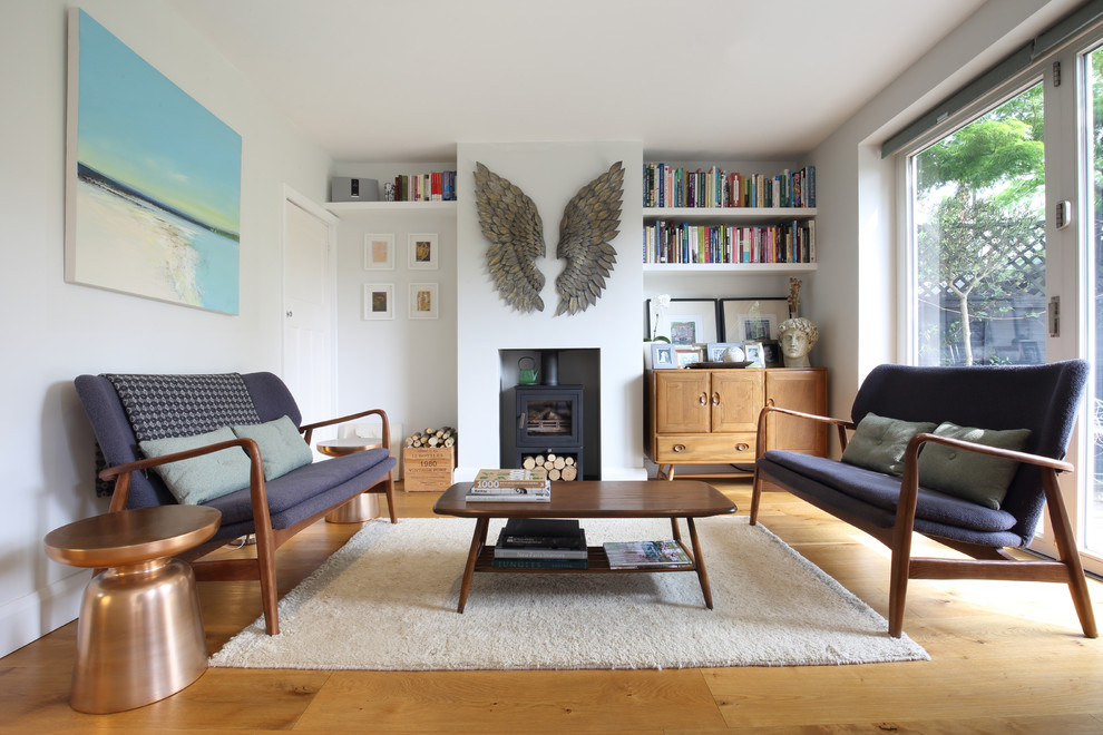 Inspiration for a mid-sized scandinavian light wood floor living room remodel in Other with a wood stove and no tv