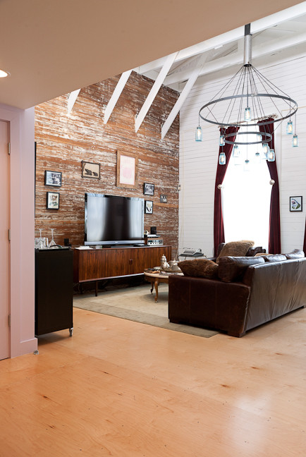 Example of a small eclectic loft-style light wood floor and brown floor living room design in San Francisco with white walls and a tv stand