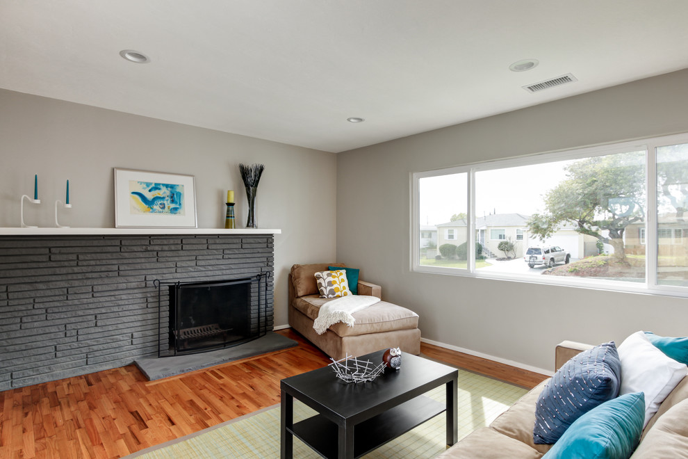 Inspiration for a mid-sized modern open concept and formal light wood floor living room remodel in San Diego with gray walls, a standard fireplace, a brick fireplace and no tv