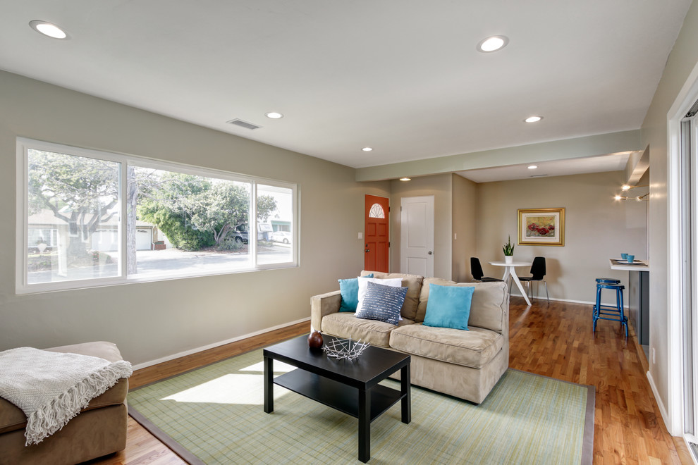 Example of a mid-sized minimalist open concept light wood floor living room design in San Diego with gray walls, a standard fireplace, a brick fireplace and no tv
