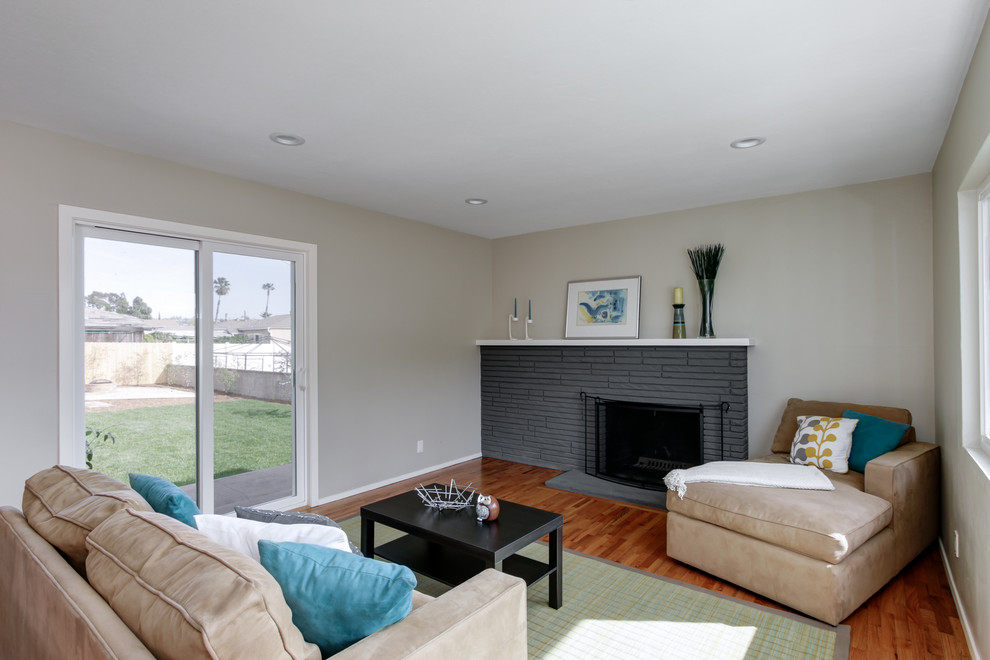 Mid-sized minimalist open concept light wood floor living room photo in San Diego with gray walls, a standard fireplace, a brick fireplace and no tv