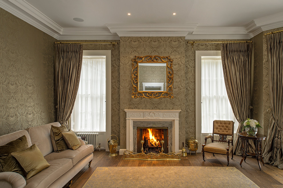 Example of a large classic formal and open concept medium tone wood floor living room design in Dublin with gray walls, a standard fireplace and a wood fireplace surround