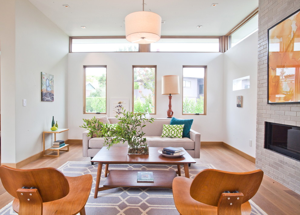 Example of a trendy medium tone wood floor living room design in Los Angeles with white walls and a ribbon fireplace
