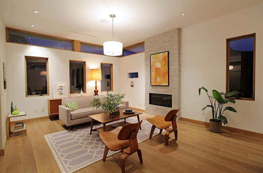 Inspiration for a large 1960s formal and open concept medium tone wood floor living room remodel in Los Angeles with white walls, a standard fireplace and a brick fireplace