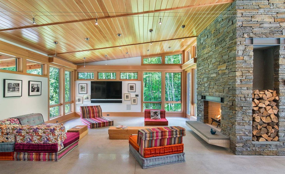 Inspiration for a contemporary open concept concrete floor and gray floor living room remodel in Burlington with white walls, a standard fireplace, a stone fireplace and a wall-mounted tv
