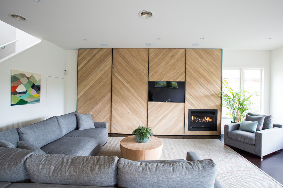 Example of a dark wood floor living room design in Melbourne with white walls, a media wall and a ribbon fireplace