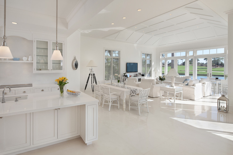 Example of an island style white floor living room design in Miami with white walls and a wall-mounted tv