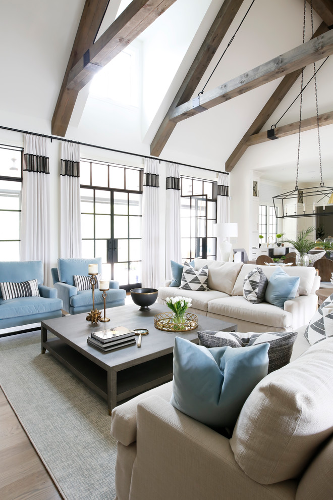 Example of a transitional open concept light wood floor living room design in Nashville with white walls