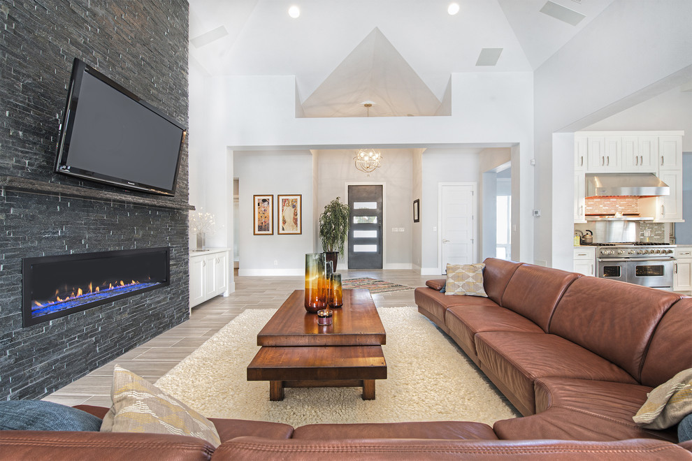 Inspiration for a transitional formal and open concept living room remodel in Austin with gray walls, a ribbon fireplace, a stone fireplace and a wall-mounted tv