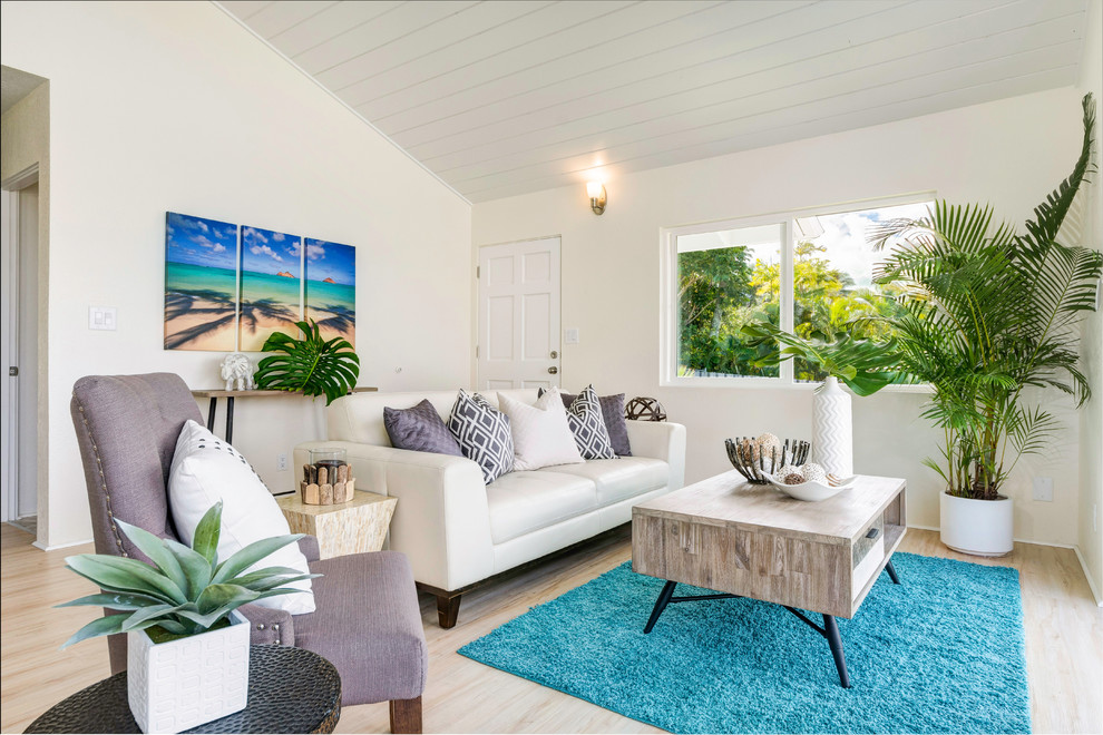 Coastal light wood floor living room photo in Hawaii with white walls