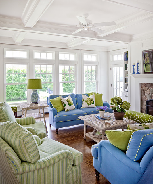 Example of a coastal enclosed medium tone wood floor and brown floor living room design in Portland Maine with white walls, a stone fireplace and a wall-mounted tv