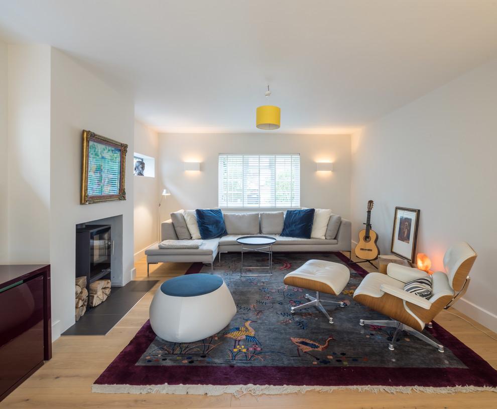 Idee per un soggiorno minimal di medie dimensioni e chiuso con sala formale, pareti bianche, parquet chiaro e stufa a legna