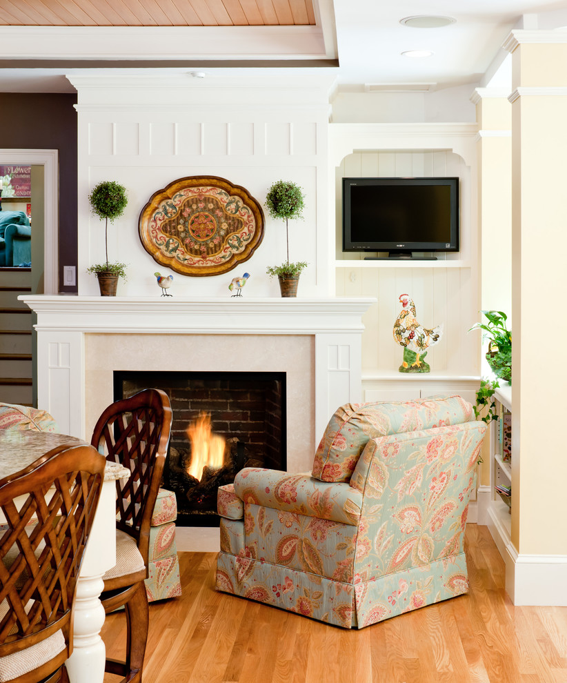 Inspiration for a timeless medium tone wood floor living room remodel in Boston with a standard fireplace and a tv stand