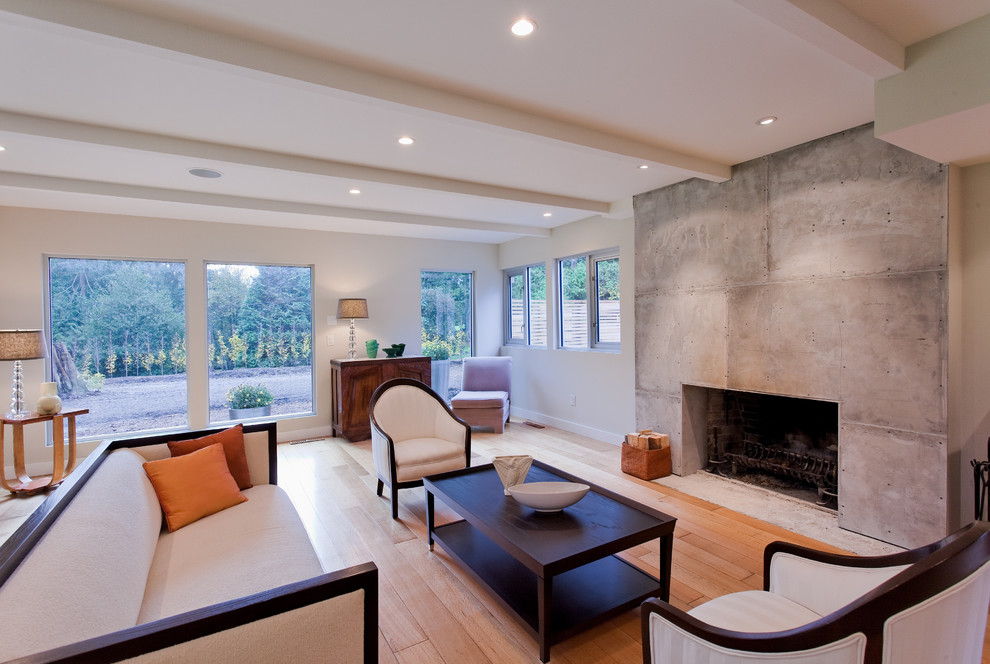 Example of a large trendy formal and open concept light wood floor and brown floor living room design in Vancouver with a standard fireplace, a concrete fireplace, beige walls and no tv