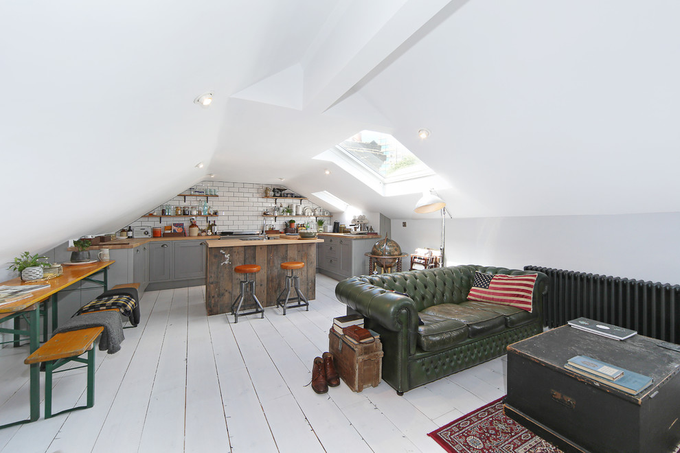 Example of a small danish open concept light wood floor and white floor living room design in London