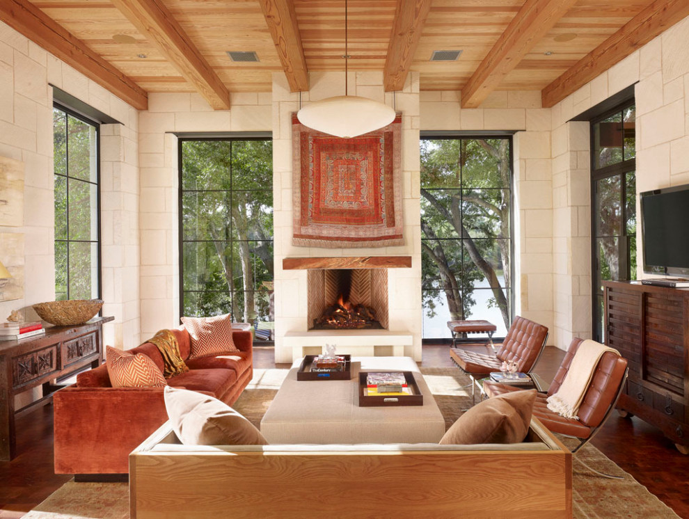Example of a large tuscan formal and open concept brown floor, dark wood floor, exposed beam and wood ceiling living room design in Austin with white walls, a standard fireplace, a plaster fireplace and a tv stand
