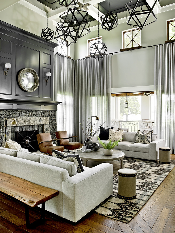 Transitional formal medium tone wood floor living room photo in Milwaukee with gray walls, a standard fireplace and a stone fireplace