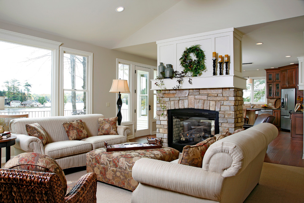 Inspiration for a large timeless formal and open concept dark wood floor and brown floor living room remodel in Grand Rapids with a stone fireplace, beige walls, a two-sided fireplace and no tv