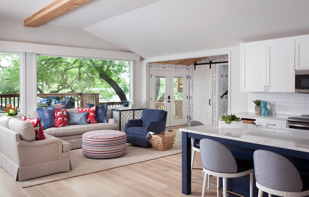 Inspiration for a mid-sized coastal open concept light wood floor and brown floor living room remodel in Austin with gray walls, a standard fireplace, a stone fireplace and a wall-mounted tv