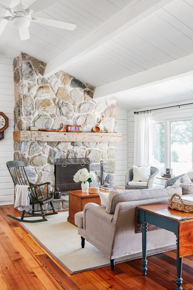Inspiration for a mid-sized coastal open concept medium tone wood floor and brown floor living room remodel in Toronto with white walls, a standard fireplace, a stone fireplace and no tv