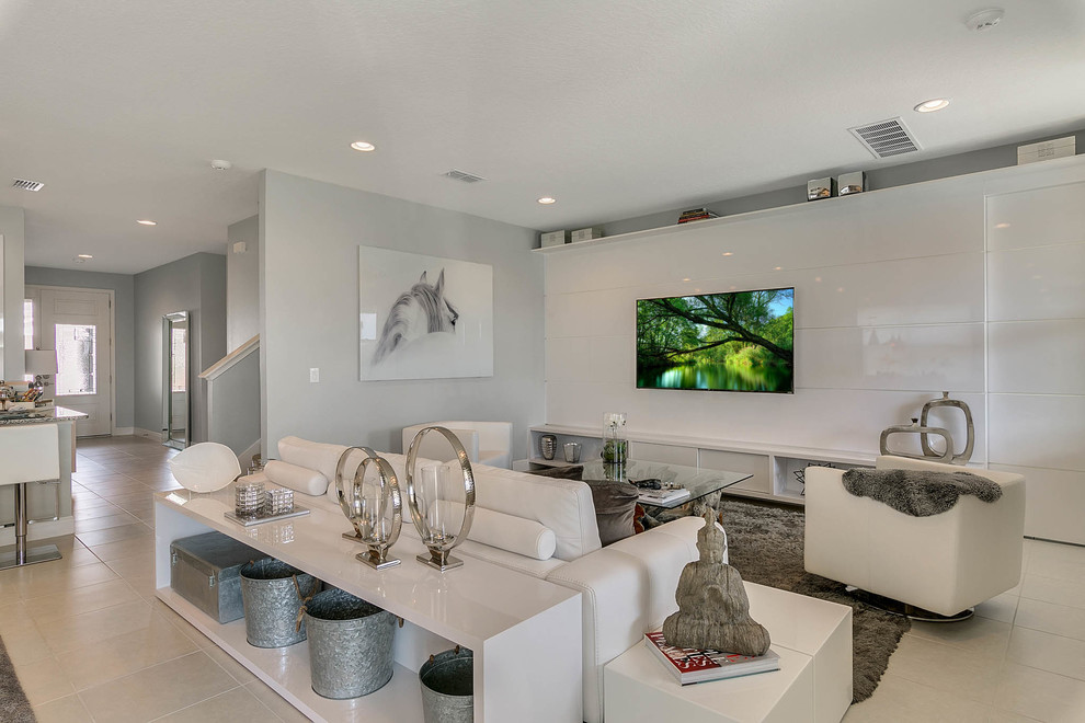Example of a trendy open concept gray floor living room design in Orlando with gray walls and a wall-mounted tv