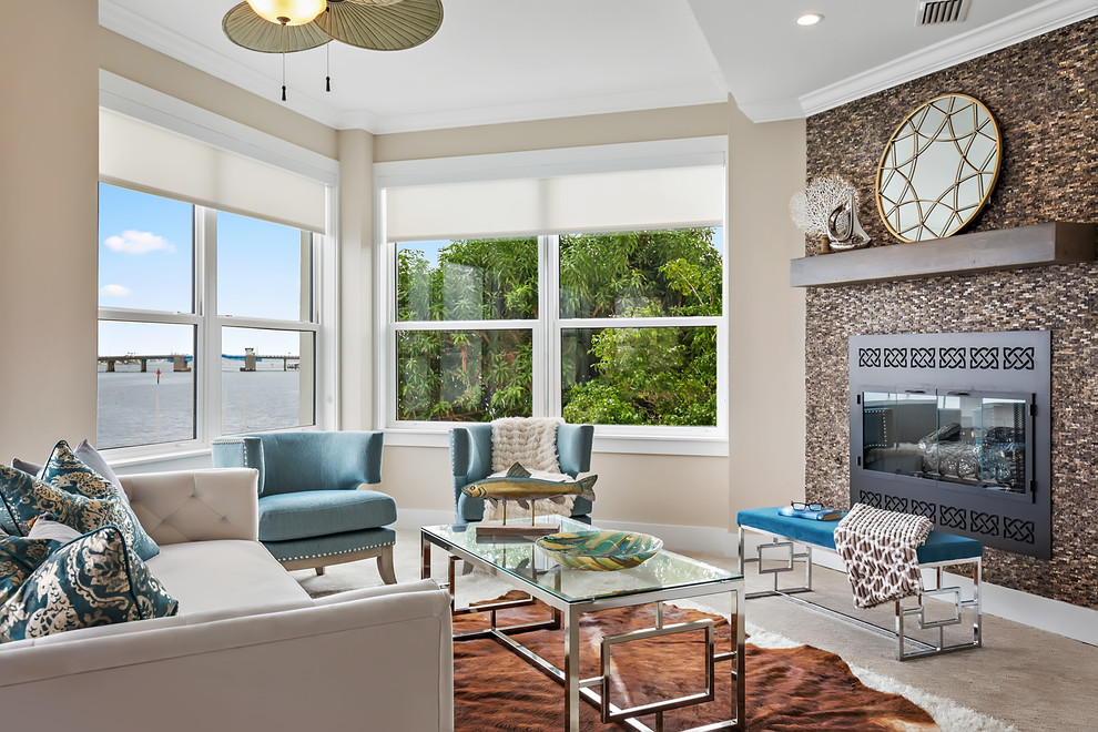 Beach style beige floor living room photo in Tampa with beige walls, a standard fireplace and a metal fireplace