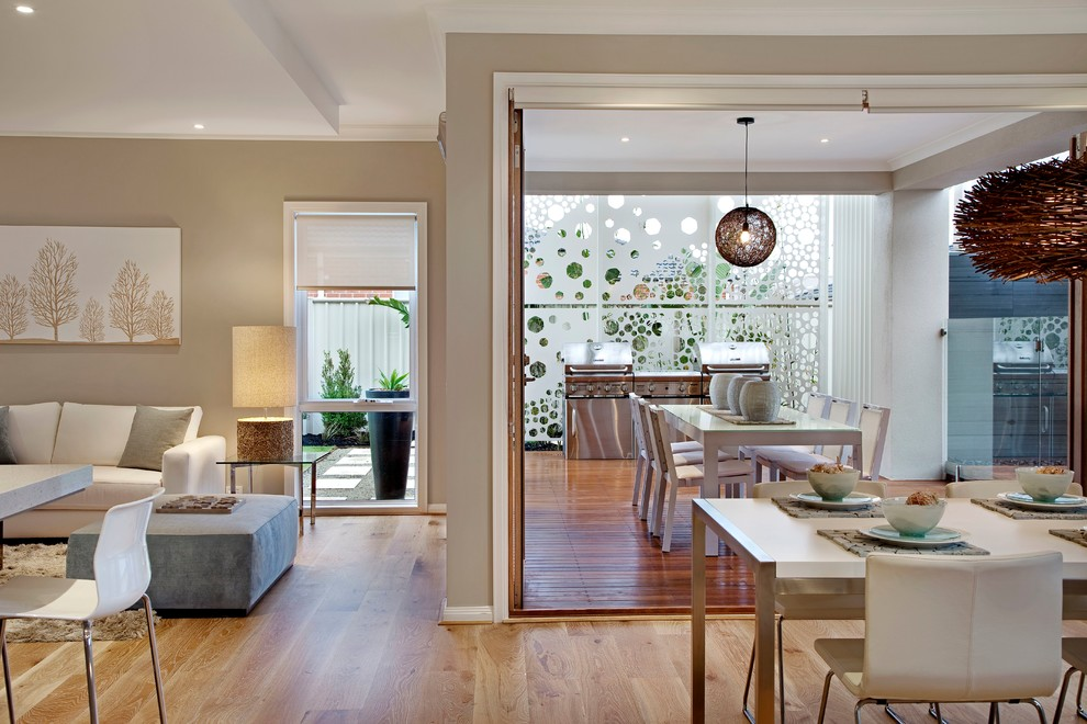 Inspiration for a contemporary open concept medium tone wood floor living room remodel in Melbourne with beige walls