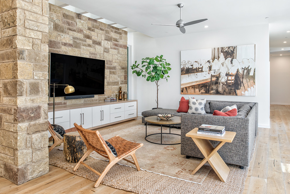Eclectic formal and open concept light wood floor and brown floor living room photo in Austin with white walls and a wall-mounted tv