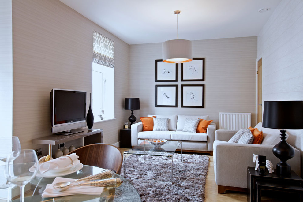 Example of a trendy light wood floor living room design in Edinburgh with beige walls and a tv stand