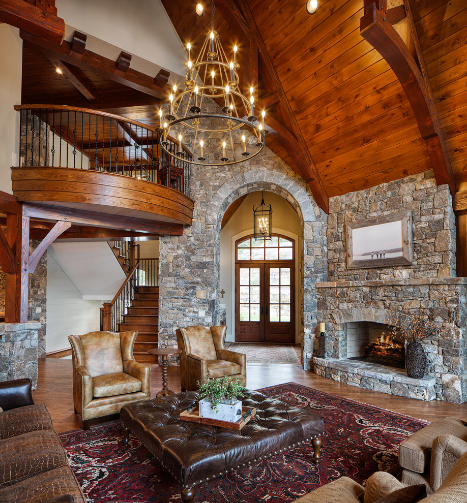 Mountain style medium tone wood floor and brown floor living room photo in Other with gray walls, a standard fireplace and a stone fireplace