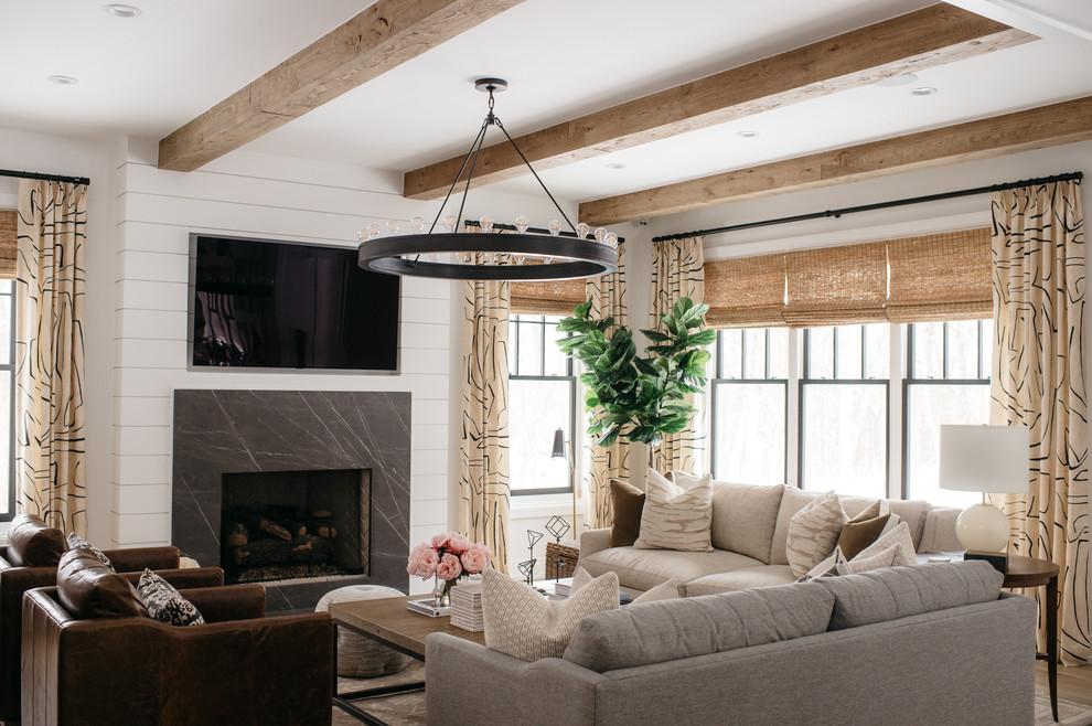 Стильный дизайн: гостиная комната в стиле кантри с белыми стенами, светлым паркетным полом, стандартным камином, фасадом камина из камня, телевизором на стене и бежевым полом - последний тренд