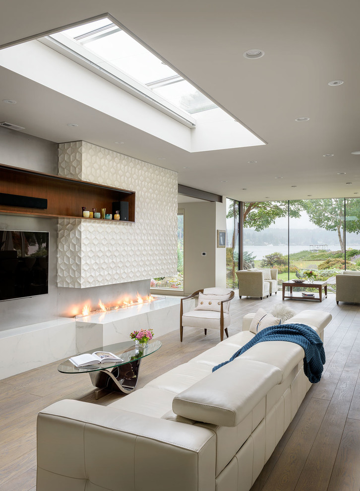 Example of a minimalist open concept medium tone wood floor and brown floor living room design in Seattle with a ribbon fireplace and a tile fireplace