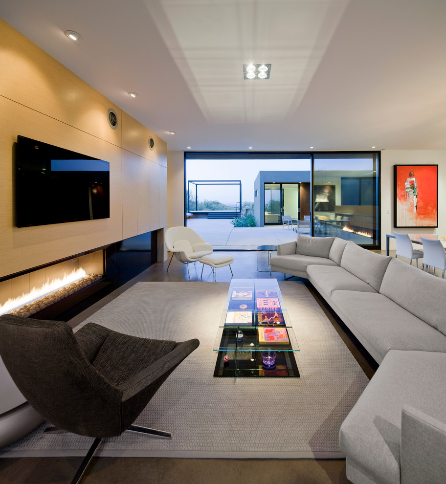 Example of a minimalist open concept concrete floor living room design in Phoenix with white walls, a ribbon fireplace and a wall-mounted tv