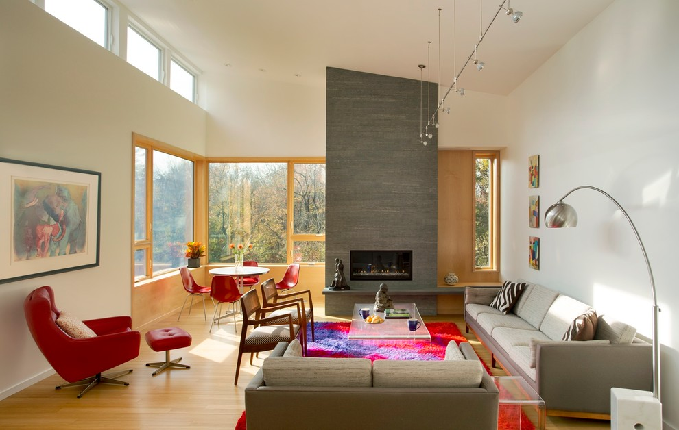 Example of a large trendy open concept light wood floor living room design in Boston with white walls and a ribbon fireplace