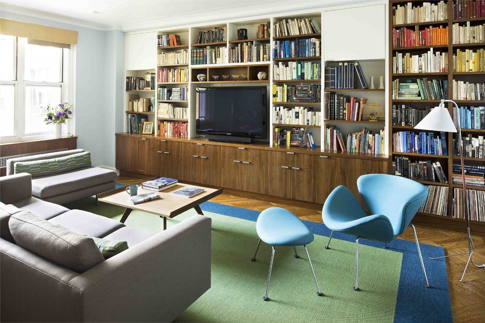 Example of a minimalist living room library design in New York with blue walls and a media wall