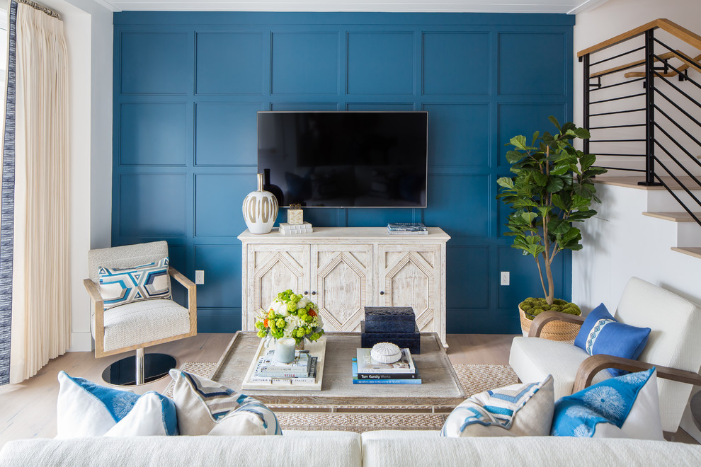 Example of a beach style light wood floor and beige floor living room design in Orange County with blue walls