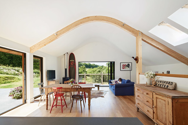 Inspiration for a rural open plan living room in Devon with white walls, medium hardwood flooring, a hanging fireplace and a freestanding tv.