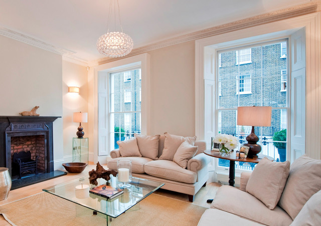 This is an example of a traditional formal living room in London with beige walls, medium hardwood flooring, a standard fireplace and no tv.
