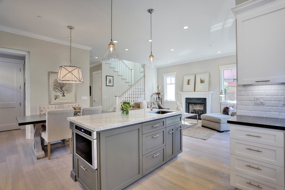 Inspiration for a mid-sized transitional open concept light wood floor living room remodel in San Francisco with gray walls, a standard fireplace, a stone fireplace and no tv