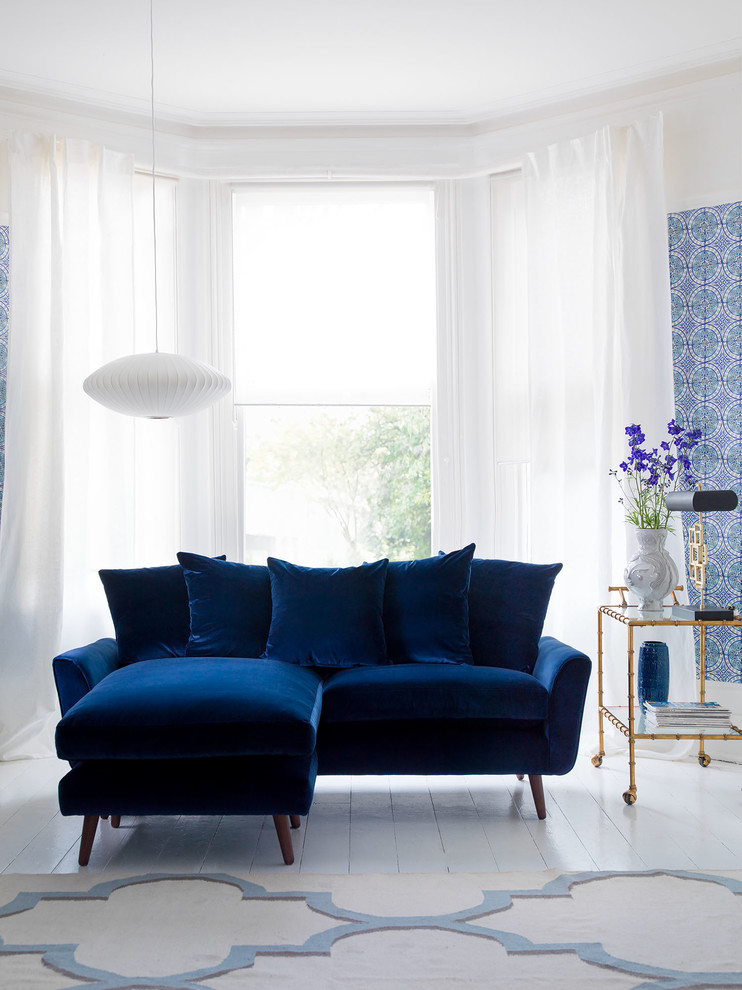 Example of a small trendy living room design in London with blue walls