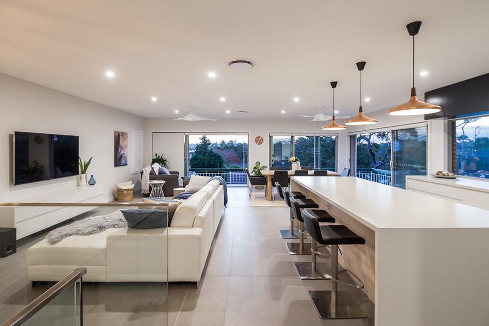 Ejemplo de salón abierto, minimalista, extra grande, con suelo de baldosas de cerámica, paredes blancas y televisor colgado en la pared