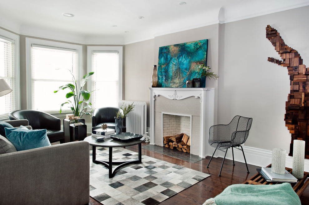 Example of a mid-sized trendy brown floor living room design in Toronto with gray walls, a standard fireplace and no tv