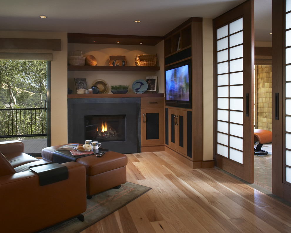 Example of a trendy living room design in San Francisco with beige walls, a standard fireplace and a media wall